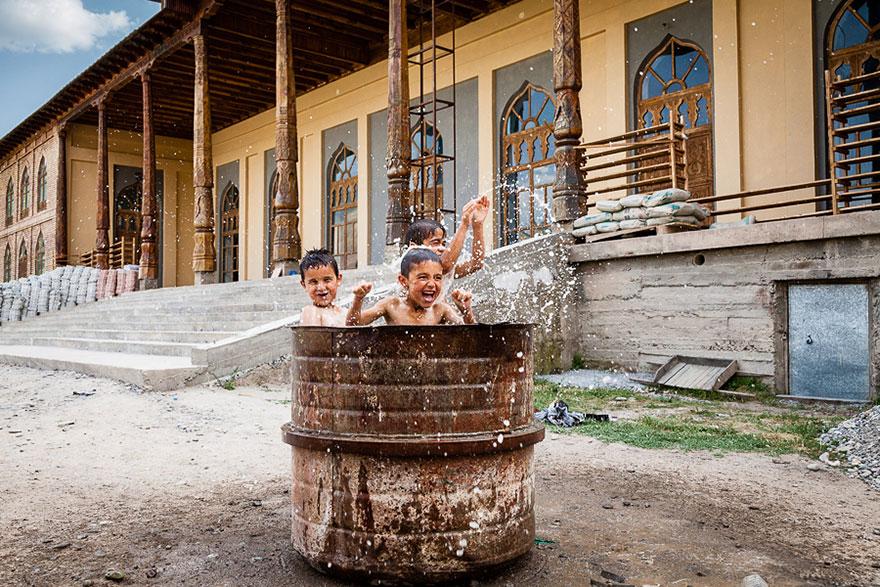 Crianças tomando banho no balde